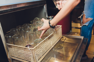 Loading glass into a dishwasher in a restaurant in Westmont, Illinois
